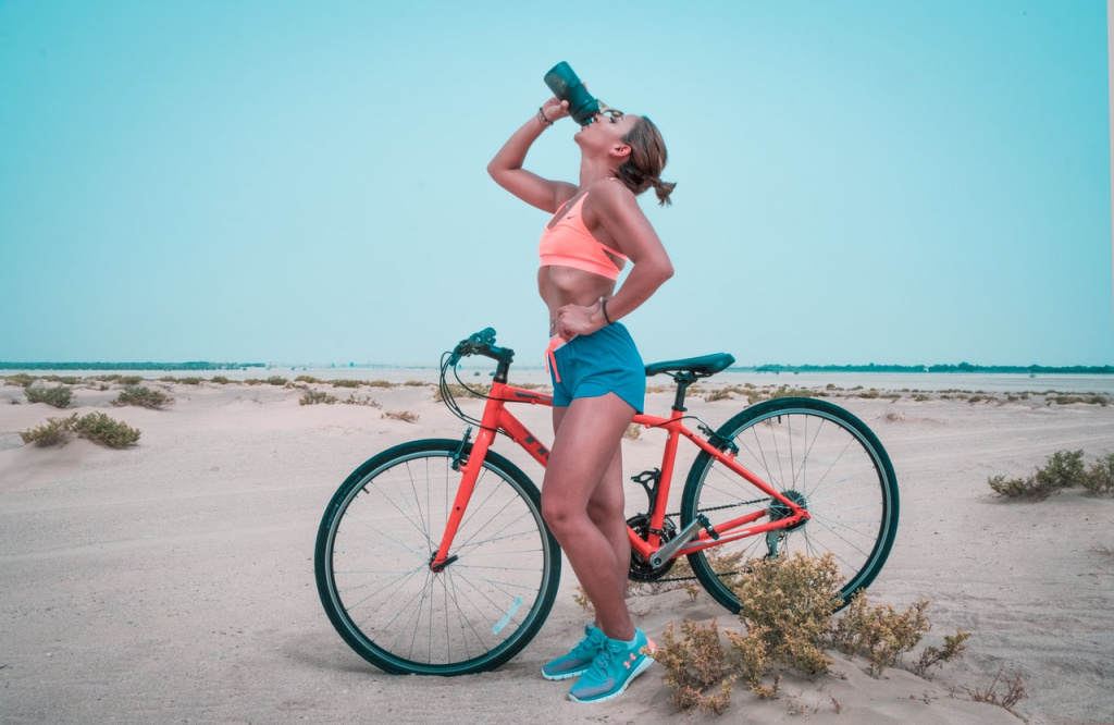 fit woman drinking water while resting on a bike